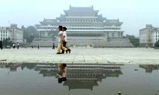 James Gourley ⋯ Two women stroll through Kim Il-sung Square in front of the Grand People's Study House